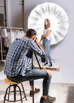 Fotógrafo tirando uma foto de um modelo de mulher
