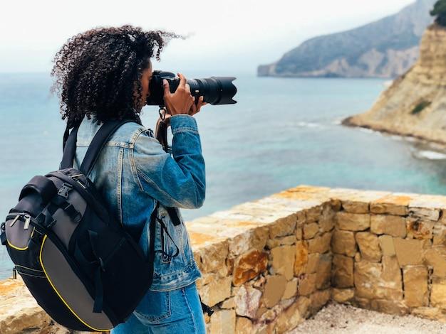 Fotógrafo tirando uma foto de uma costa do oceano
