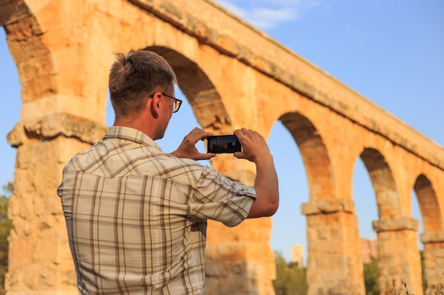 Fotógrafo tirando uma foto do antigo aqueduto romano de tarragona, espanha.