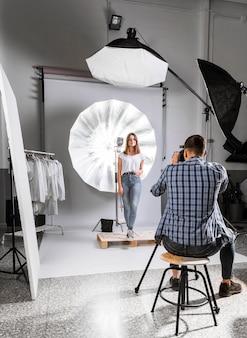Fotógrafo tirando uma foto do modelo feminino