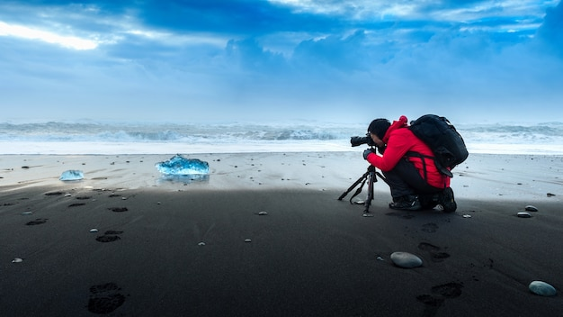 Fotógrafo tirando uma foto no gelo na islândia.
