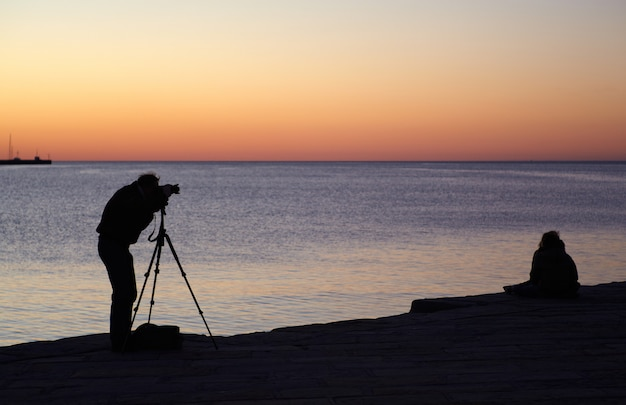 Fotógrafo tirar uma foto ao pôr do sol