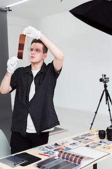 Fotógrafo, trabalhando em seu estúdio com tiras de foto