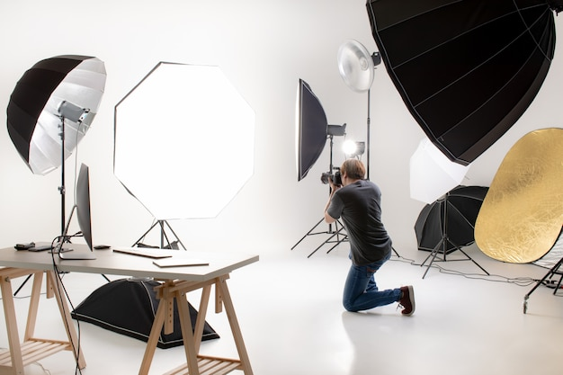 Fotógrafo trabalhando no estúdio de iluminação moderna com muitos tipos de flash e acessórios