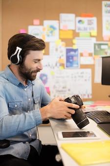 Fotógrafo usando fones de ouvido enquanto usa a câmera