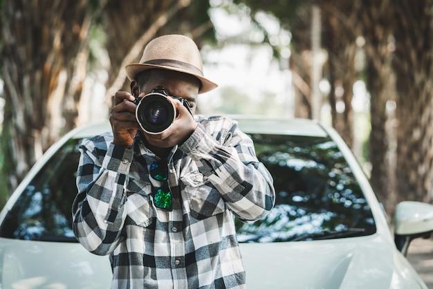 Fotógrafo viajante africano homem na estrada com carro branco e câmera fotográfica tirando