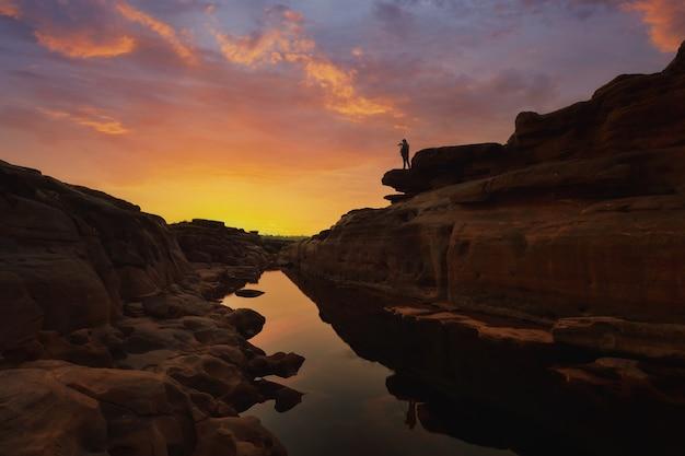 Fotógrafo viajante que tira uma foto do céu estrelado e do nascer do sol nas montanhas
