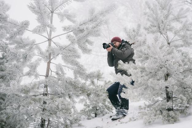 Fotógrafo viajante tirando fotos na floresta de inverno