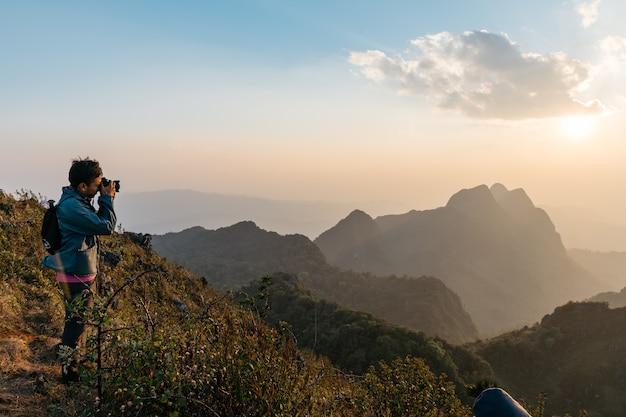 Fotógrafos de aventura tirando fotos de montanhas e paisagens ao entardecer perto do pôr do sol em doi luang chiang dao