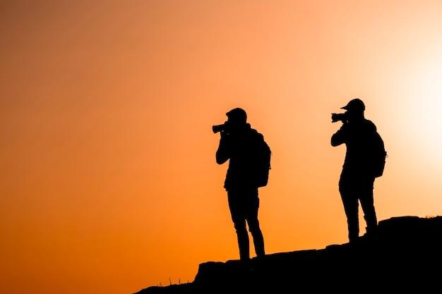 Fotógrafos de silhuetas que fotografam um pôr do sol nas montanhas. conceito de fotógrafo