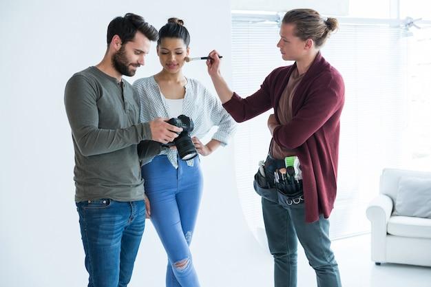 Fotógrafos e modelo feminino olhando imagens no visor da câmera