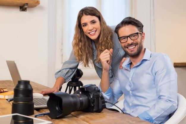 Fotógrafos profissionais com câmera e laptop trabalhando no estúdio. fotógrafo com assistente sentado no escritório e. equipe de fotógrafos trabalhando juntos.