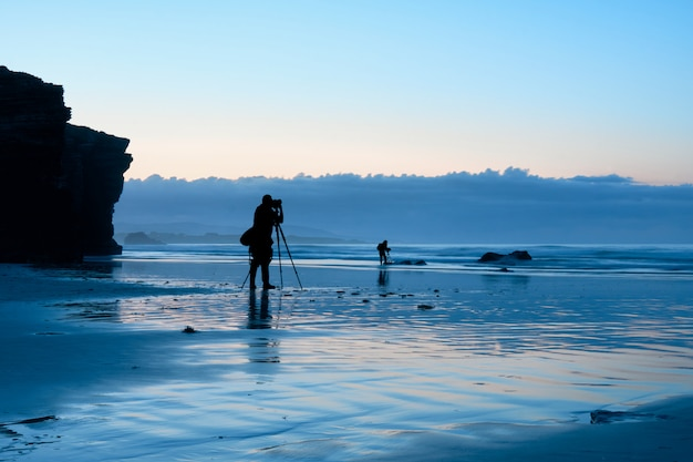 Fotógrafos que trabalham na praia durante a hora azul