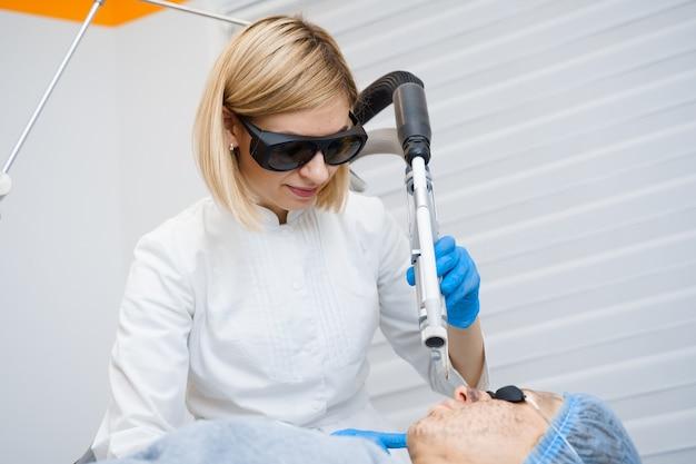 Fotorejuvenescimento a laser e peeling de carbono de rosto para mulher. máscara facial preta. dermatologia e cosmetologia. usando laser cirúrgico.