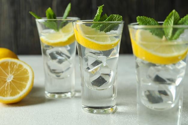 Fotos com rodelas de limão e hortelã na mesa texturizada branca