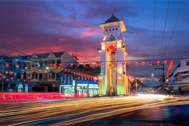 Fotos da cidade de yala, na tailândia, à noite, as luzes do carro em execução que é o marco de yala, torre do relógio e túnel do carro