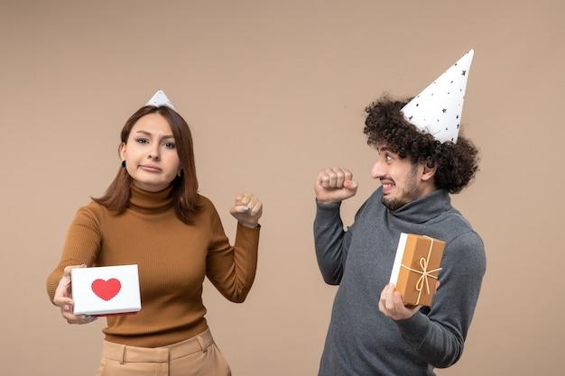 Fotos de ano novo com um jovem casal emocional chocado e louco usando uma garota de chapéu de ano novo com coração