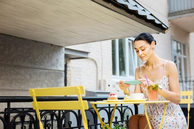 Fotos de comida. alegre blogueira popular se sentindo satisfeita enquanto está sentada em um café ao ar livre e tirando fotos de suas refeições