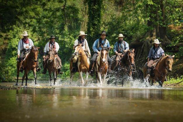 Fotos de muitos homens vestindo roupas de cowboy, cavalgando e viajando pelo rio