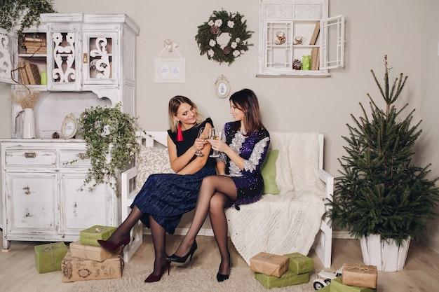 Fotos de natal de lindas amigas em vestidos de noite rodeadas de presentes