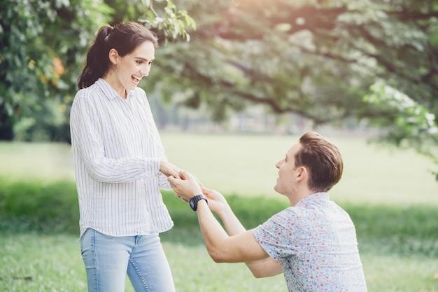 Fotos de noivados, propostas de casamento e casais recém-noivos que amam o jovem e a senhora no parque verde ao ar livre.