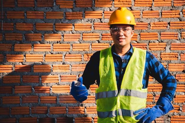 Fotos de trabalhadores da construção civil asiáticos no canteiro de obras ou fotos de trabalhadores da construção civil no canteiro de obras mon brick background