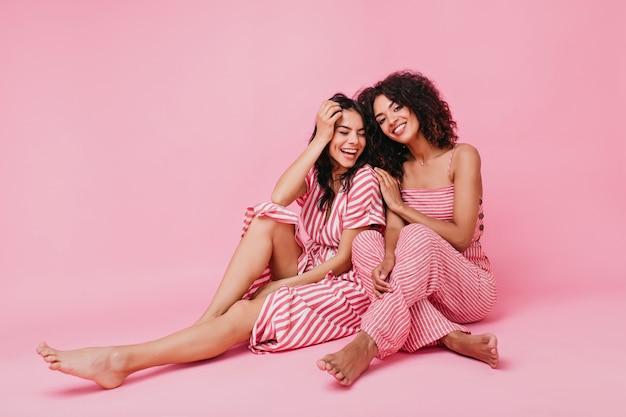 Fotos de verão brilhantes de melhores amigos em alto astral. menina com covinhas no rosto ri enquanto a irmã olha afetuosamente