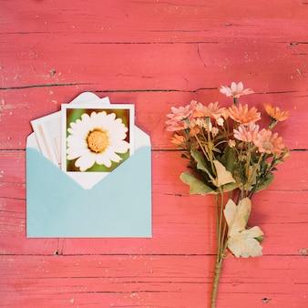 Fotos instantâneas em um envelope com buquê de margaridas