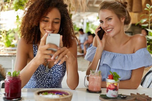 Fotos internas de mulheres felizes usando smartphones modernos, navegando em redes sociais e conversando pelo celular, passando o tempo livre no refeitório, bebendo smoothie. mulheres alegres recriam durante as férias de verão