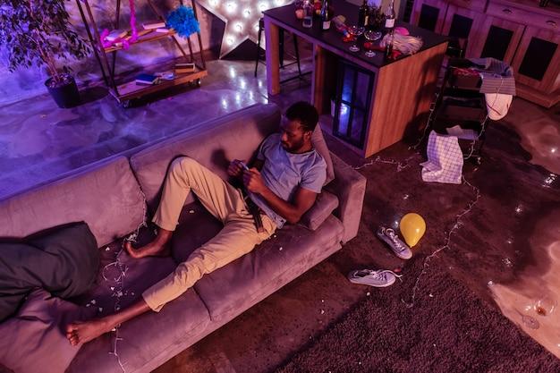 Fotos no smartphone. homem afro-americano concentrado experimentando efeito negativo do consumo de álcool após a festa