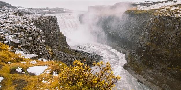 Fotos panorâmicas de cachoeiras islandêsas famosas em dias nublados com formações geological.