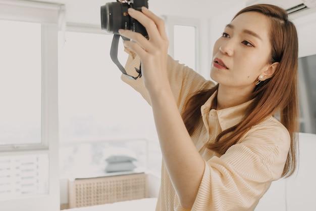 Fototógrafa de mulher verificando o visor da câmera em seu próprio apartamento.
