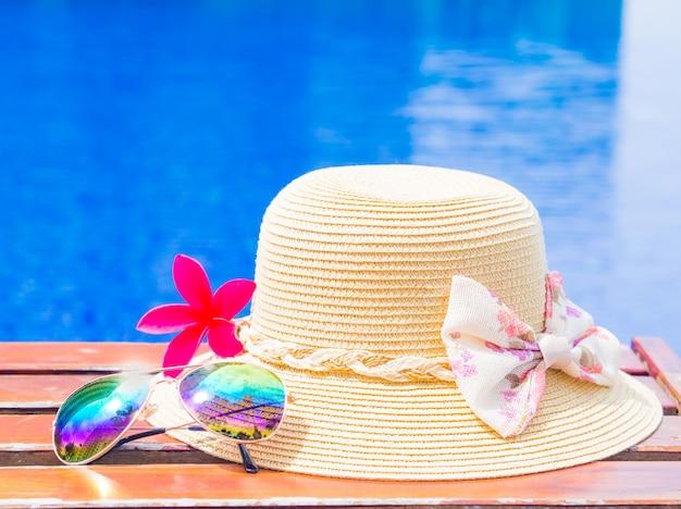 Fower com chapéu de verão e óculos de sol à beira da piscina
