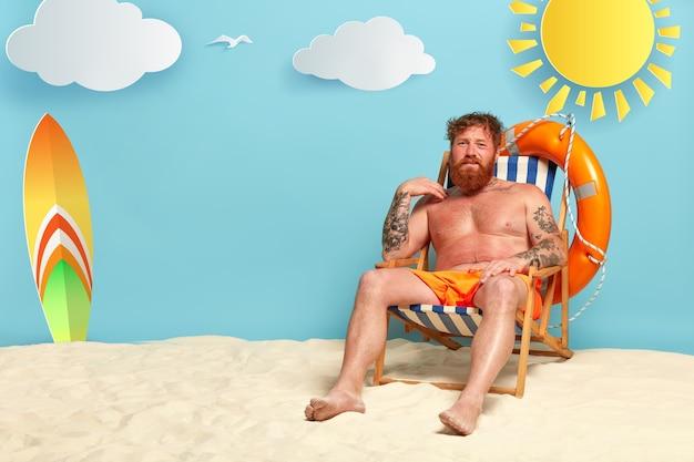 Foxy homem insatisfeito fica com queimaduras de sol na praia, tem pele vermelha, senta-se na cadeira de sol seminu
