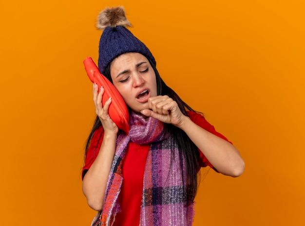 Fraca jovem caucasiana doente com chapéu de inverno e lenço tocando o rosto com bolsa de água quente tossindo, mantendo o punho fechado perto da boca com os olhos fechados, isolado na parede laranja com espaço de cópia