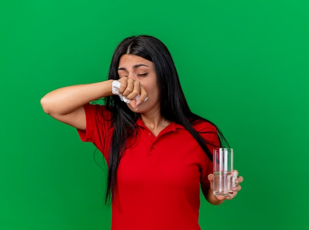 Fraca jovem caucasiana doente segurando um pacote de comprimidos, copo de água e guardanapo se preparando para espirrar, mantendo a mão no nariz com os olhos fechados, isolado na parede verde com espaço de cópia