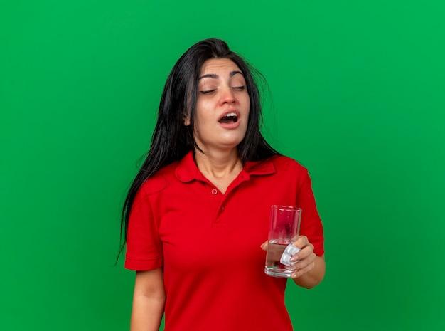 Fraca jovem caucasiana doente segurando um pacote de comprimidos, um copo de água se preparando para espirrar com os olhos fechados, isolado em um fundo verde com espaço de cópia