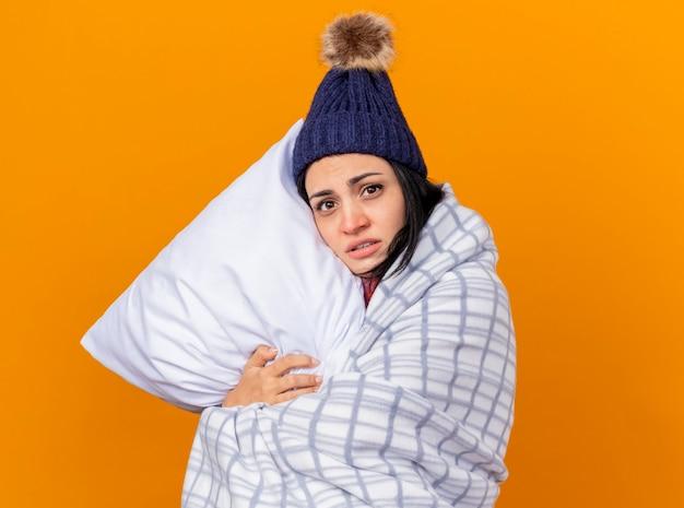 Fraca jovem caucasiana doente usando chapéu de inverno e lenço embrulhado em um travesseiro xadrez, olhando para a câmera isolada em um fundo laranja com espaço de cópia