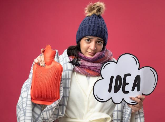 Fraca jovem caucasiana doente vestindo um manto de inverno, chapéu e cachecol embrulhado em xadrez, segurando uma bolsa de água quente e uma bolha de ideia isolada na parede carmesim