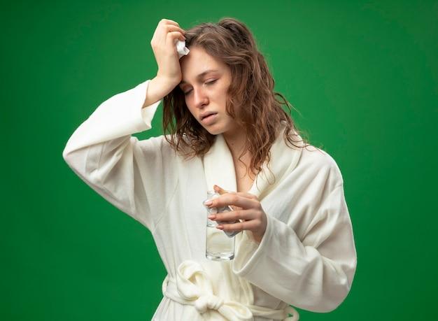 Fraca jovem doente com os olhos fechados, usando um manto branco, segurando um copo d'água e colocando a mão na testa isolada no verde