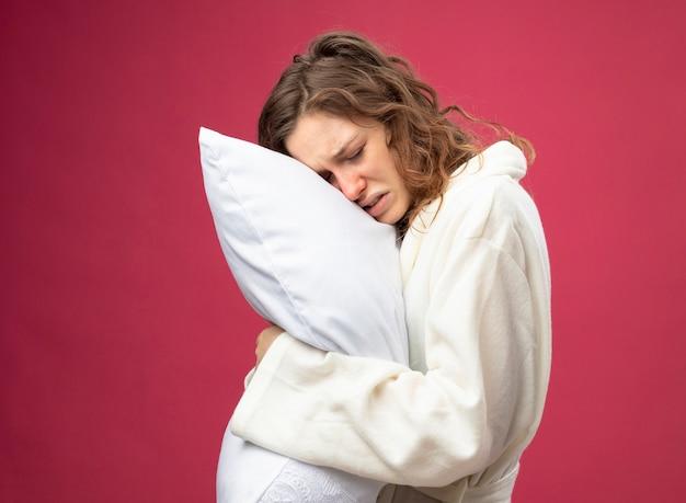 Fraca jovem doente com os olhos fechados, vestindo uma túnica branca abraçada com um travesseiro isolado em rosa