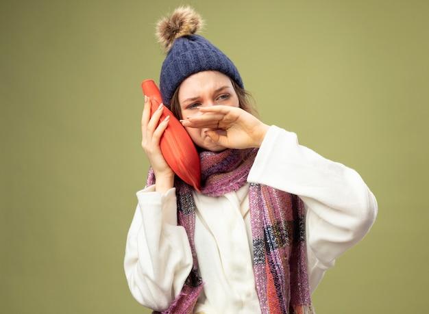 Fraca jovem doente olhando para o lado usando túnica branca e chapéu de inverno com lenço colocando uma bolsa de água quente na bochecha e limpando o nariz com a mão isolada em verde oliva