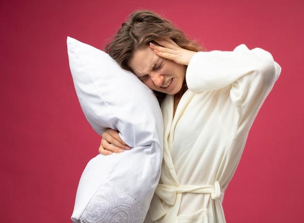 Fraca jovem doente vestindo um manto branco abraçou o travesseiro, colocando a mão na cabeça dolorida isolada no rosa