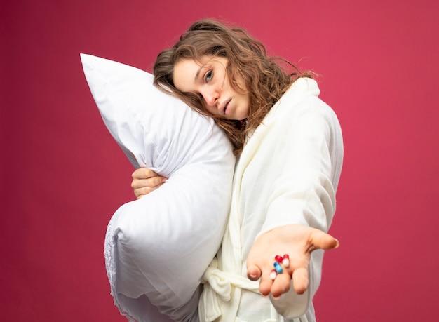 Fraca jovem doente vestindo um manto branco abraçou o travesseiro segurando pílulas isoladas em rosa