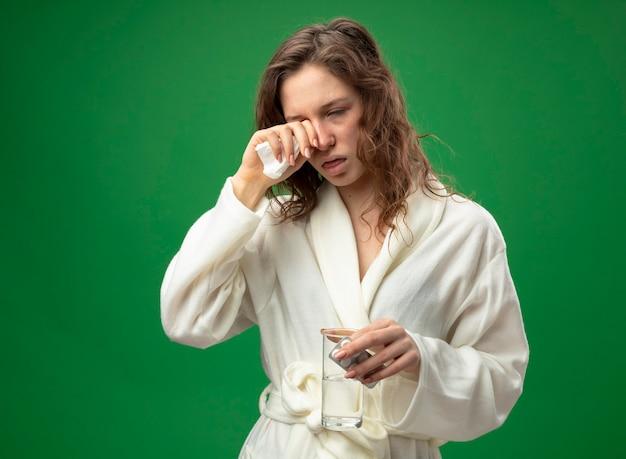 Fraca jovem doente vestindo um manto branco, segurando um copo de água com comprimidos e limpando os olhos com a mão isolada no verde com espaço de cópia