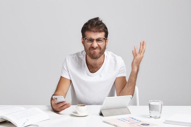Fracasso, colapso nervoso e estresse no trabalho. jovem gerente europeu estressado e zangado com a barba fazendo caretas e gesticulando