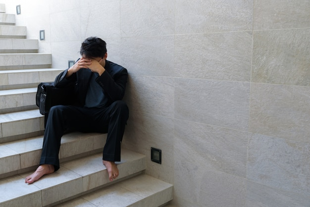 Fracasso nos negócios jovens empresários sentam-se nas escadas e suas mãos apertaram a cabeça. porque ele está tão desesperado, estressado, tristeza depois de saber as más notícias de que está desempregado.