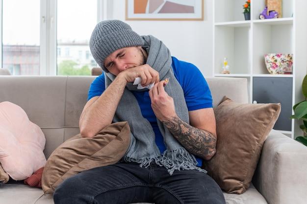 Fraco, jovem, doente, usando cachecol e chapéu de inverno, sentado no sofá na sala de estar, segurando um pacote de cápsulas e guardanapo, limpando o nariz com a mão com os olhos fechados