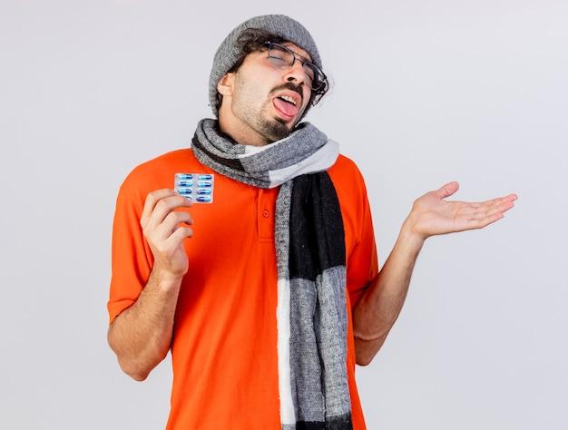 Fraco, jovem, doente, usando óculos, chapéu e lenço de inverno, mostrando o pacote de cápsulas e a mão vazia, mostrando a língua com os olhos fechados, isolado na parede branca