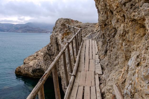 Frágil velha ponte podre sobre as rochas na costa do mar
